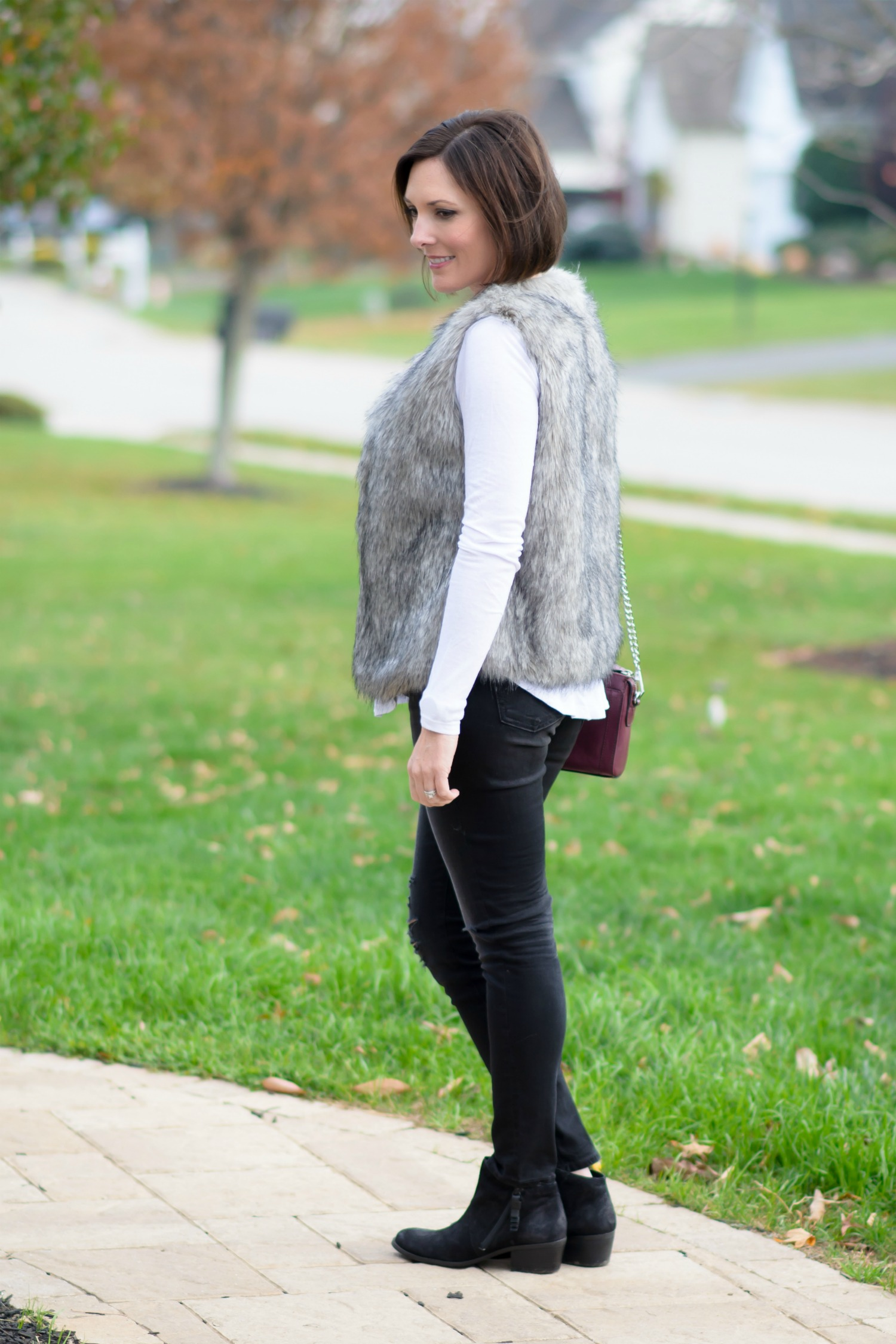 Winter Outfit Ideas: Fur Vest with Distressed Jeans and Long Sleeve Tee