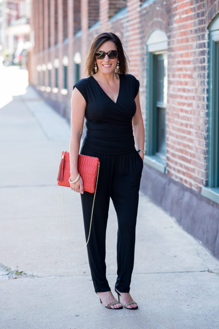 How to Wear a Jumpsuit: Pair a black jumpsuit with high heeled leopard sandals, and add a bright clutch.