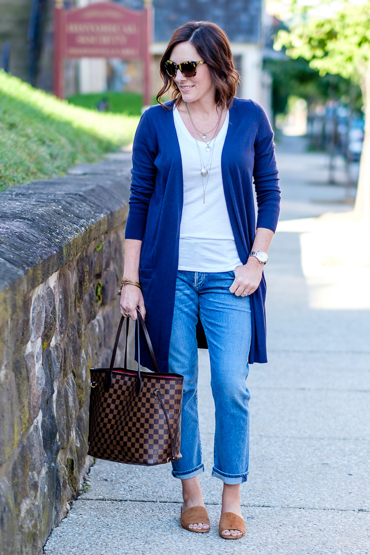 Jo-Lynne Shane styling slim boyfriend jeans for fall with a long navy cardigan and cognac suede slides.
